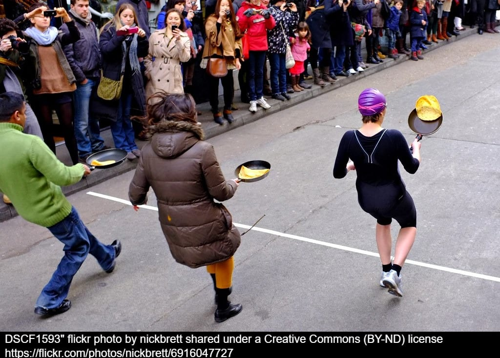 Three adults in a pancake day race